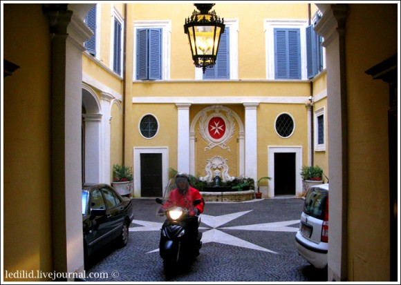 Работник на скутере выезжает из Палаццо Мальта