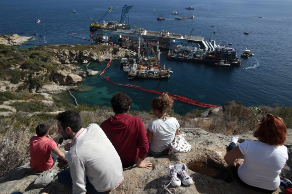 People look on at the operation of salvation the capsized cruise liner Costa Concordia