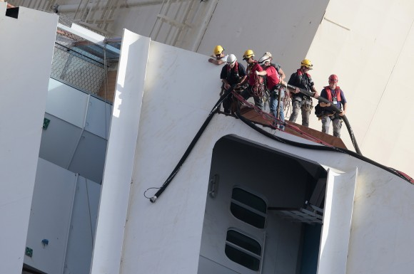Salvage crew workers work on a side of the capsized Costa Concordia   during the salvation